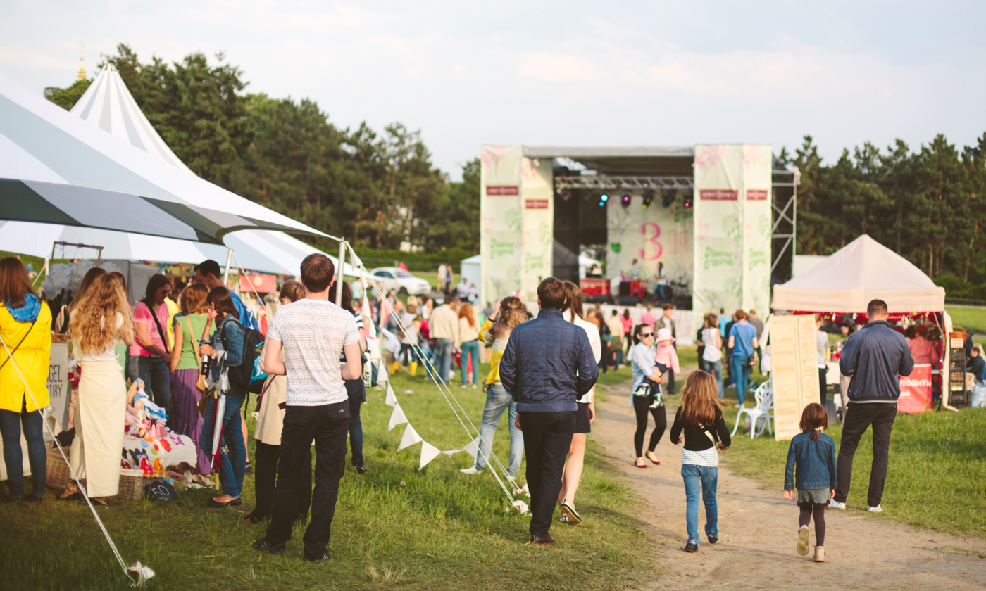 People walking on festival grounds toward a stage