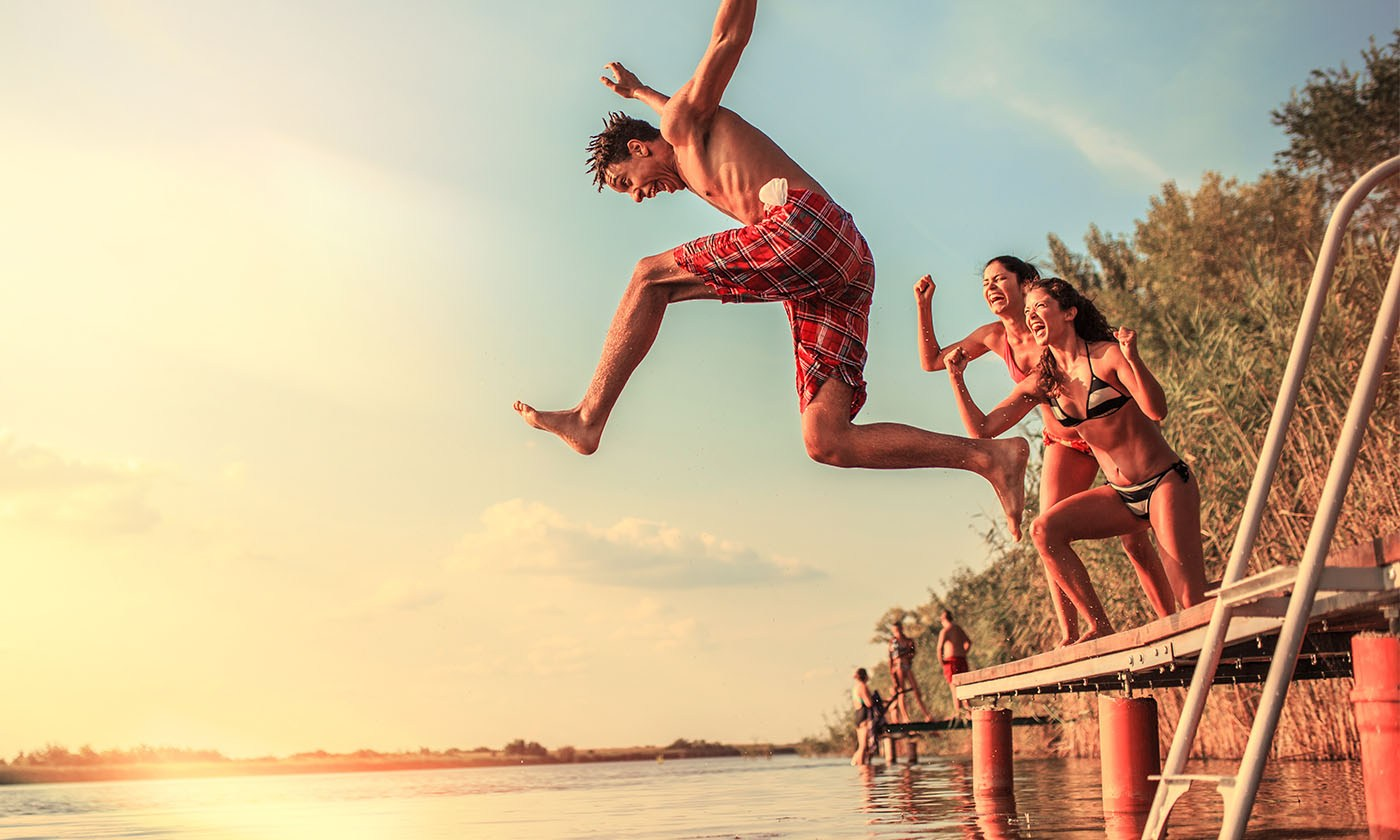 Guy in swim trunks jumping off of a dock into a lake