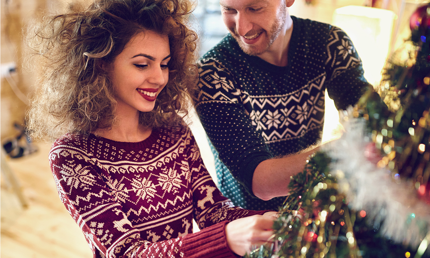 Couple Smiling While Decorating Christmas Tree